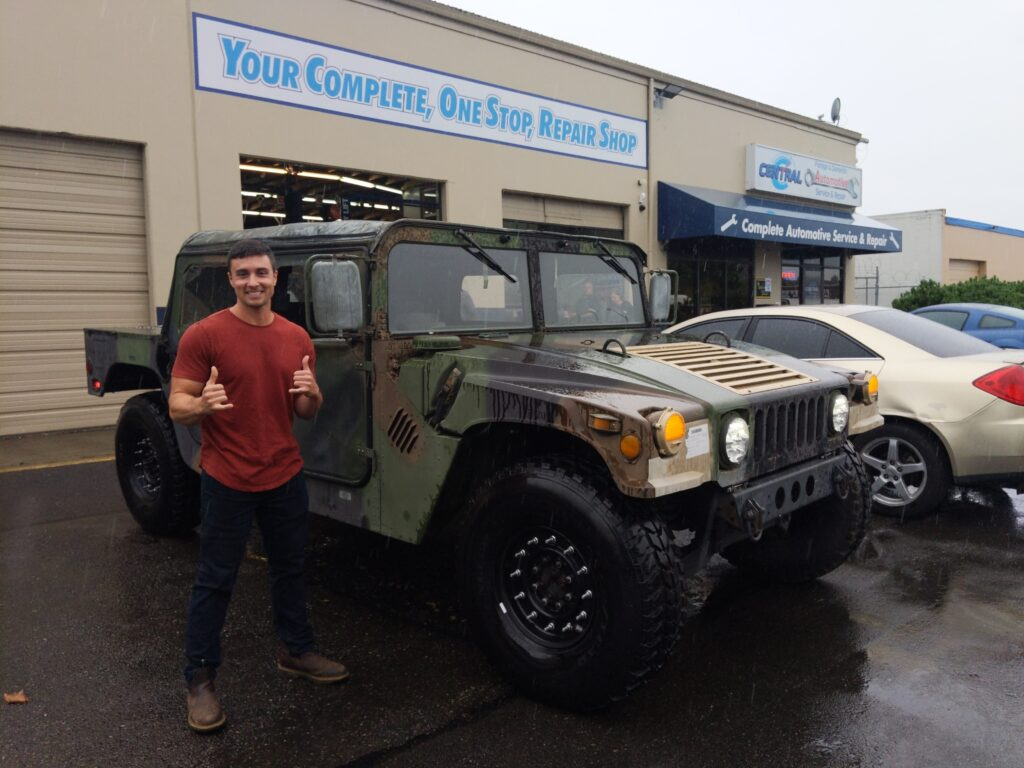 man posing next to old military SUV